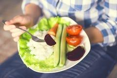 Une fille tient un plat avec du riz et des légumes image stock