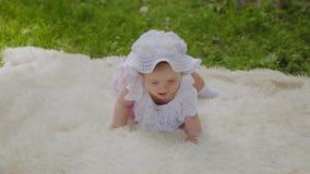 Une fille très petite et belle jouant sur le couvre-lit en parc clips vidéos
