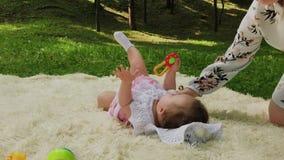 Une fille très petite et belle jouant sur le couvre-lit en parc banque de vidéos