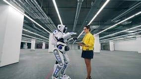 Une fille travaille avec un comprimé, commandant un droid blanc clips vidéos