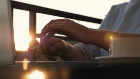 Une fille travaille avec un ordinateur portable et une tasse de café à une table au coucher du soleil au soleil banque de vidéos