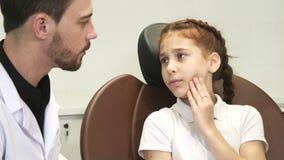 Une fille triste décrit son mal de dents au docteur photo stock