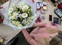 Une fille, un fleuriste-concepteur donne un beau, de fête bouquet des fleurs rouges photos stock