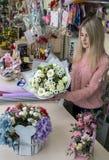 Une fille, un fleuriste-concepteur donne un beau, de fête bouquet des fleurs rouges photographie stock