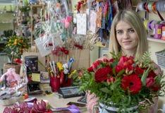 Une fille, un fleuriste-concepteur donne un beau, de fête bouquet des fleurs rouges et un coeur avec l'amour d'inscription, parti photographie stock