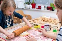Une fille utilise la goupille pour dérouler la pâte sur l'étiquette image libre de droits
