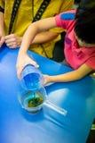 Une fille versant la solution chimique bleue dans la solution acide et les obs Photo libre de droits