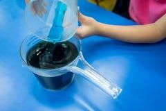 Une fille versant la solution chimique bleue dans la solution acide jusqu'à t Photographie stock libre de droits