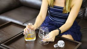 Une fille verse l'alcool d'une carafe dans un verre banque de vidéos
