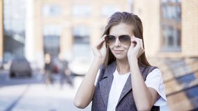 Une fin d'une jeune fille de sourire utilise des lunettes de soleil dehors image stock