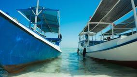 Une fin traditionnelle de bateau ancrée en bord de la mer de plage avec la mer claire transparente images libres de droits