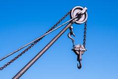 Une fin vers le haut de vue d'une grue en métal et de ses crochets a placé contre un bleu image stock