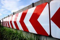 Une flèche blanche allumant un panneau routier rouge de fond Photos libres de droits