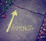 Une flèche jaune montrant la manière au bonheur Photographie stock libre de droits