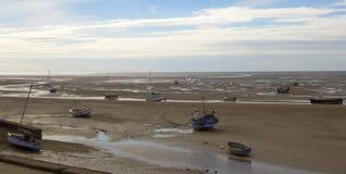 Une flotte de bateaux est partie échoué à marée basse Images stock