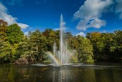 Une fontaine dans un étang, avec un arc-en-ciel Images libres de droits