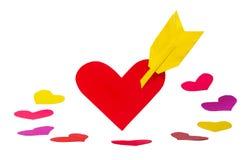 Une forme de papier rouge de coeur avec la flèche et beaucoup de peu de formes de coeur Photographie stock