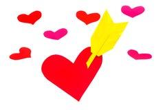 Une forme de papier rouge de coeur avec la flèche et beaucoup de peu de formes de coeur Image libre de droits