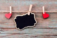 Une forme rouge de coeur et un tableau noir avec le te heureux de jour du ` s de Valentine Photographie stock