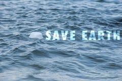 Une forme vide blanche a trouvé la gauche flotter sur le bord de mer Sauvez la terre svp ! photographie stock libre de droits