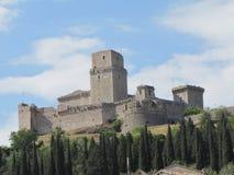 Une forteresse majestueuse donne sur la banlieue noire d'Assisi en Italie photo stock