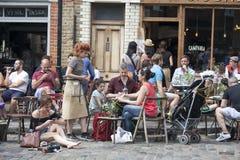 une foule bariolée de Londres est buvant d'une bière en dehors de bar Images stock