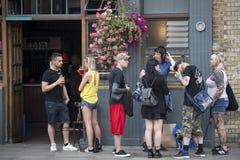 une foule bariolée de Londres est buvant d'une bière en dehors de bar images libres de droits