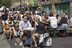 une foule bariolée de Londres est buvant d'une bière en dehors de bar Photo stock