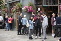 Une foule bariolée s'assied en dehors du bar, boit de la bière, parle avec des amis Marché de ville Images stock