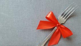Une fourchette avec un arc rouge se trouve sur la nappe Un endroit à enregistrer Photo pour le menu du café, restaurant, salle à  image stock