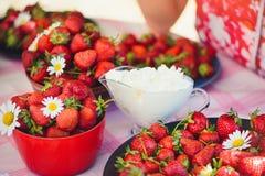 Une fraise fraîche avec de la crème dans une cuvette sur une table dans le jardin d'été est décorée des fleurs de camomille avec  photographie stock libre de droits