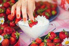 Une fraise fraîche avec de la crème dans une cuvette sur une table dans un jardin d'été est décorée des fleurs de camomille que l photographie stock