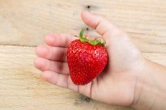Une fraise tenue par une main Photographie stock