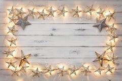 Une frontière des lumières de Noël d'or d'étoile, et des babioles d'étoile, sur a image stock