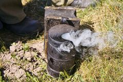 Une fum?e de soufflage de fumeur d'abeille utilis?e dans le rucher images stock