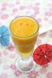 Une glace de jus d'orange sur le fond coloré Photo stock