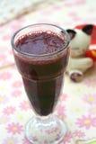 Une glace de jus de raisins sur le fond coloré Photo stock