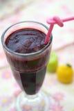 Une glace de jus de raisins sur le fond coloré Images stock