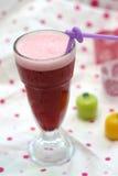 Une glace de jus de raisins sur le fond coloré Image libre de droits