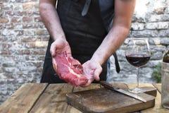 Une glace de vin rouge sur une table en bois Un homme dans un tablier en cuir noir prépare la viande de boeuf pour le dîner et un image stock