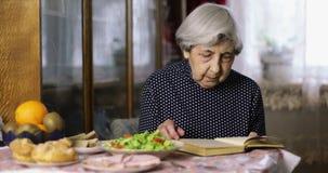 Une grand-mère avec les cheveux gris s'assied dans une chambre et lit un livre banque de vidéos