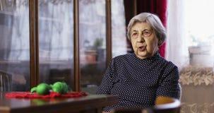 Une grand-mère avec les cheveux gris s'assied et parle banque de vidéos