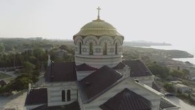 Une grande belle église sur la banque d'une rivière près de la ville projectile Vue aérienne fascinante de rive de l'église banque de vidéos