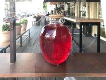 Une grande boîte lumineuse lumineuse ronde en verre transparente rouge avec un couvercle en bois, un pot de jus doux délicieux, u photos stock