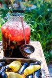 Une grande bouteille de sangria froide avec une poche sur la table de datcha Image libre de droits