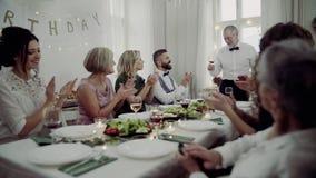 Une grande famille s'asseyant à une table sur une fête d'anniversaire d'intérieur, un homme supérieur donnant un discours banque de vidéos