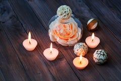 Une grande fleur rose dans un globe en verre, des décorations et de divers éléments intéressants sur un fond en bois foncé S Photographie stock libre de droits