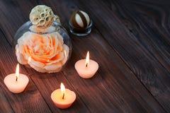 Une grande fleur rose dans un globe en verre, des décorations et de divers éléments intéressants sur un fond en bois foncé S Image libre de droits