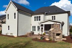Une grande maison avec l'arrière-cour aménagée en parc Image stock