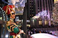Une grande statue de batteur de casse-noix de jouet et les lumières de vacances dans le Rockefeller Center images stock